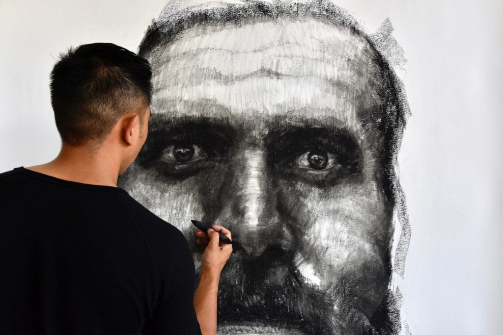 A man drawing a huge face on a wall