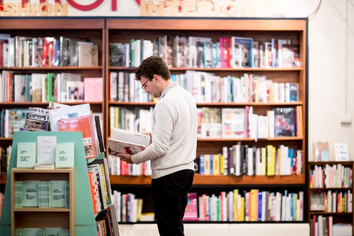 A man looking at a book surrounded by bookshelves in a bookstore