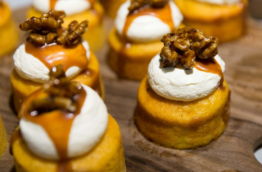 Little cakes on a board topped with cream, walnuts and syrup