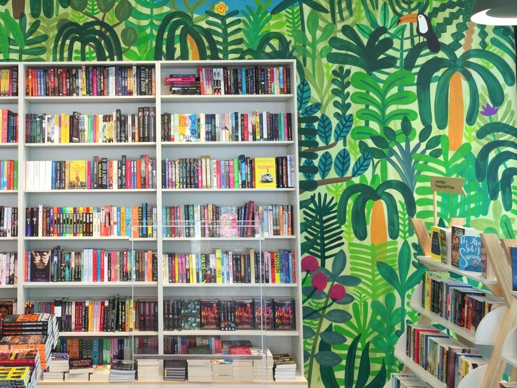 Shelves lined with books in front of a brightly coloured wall mura