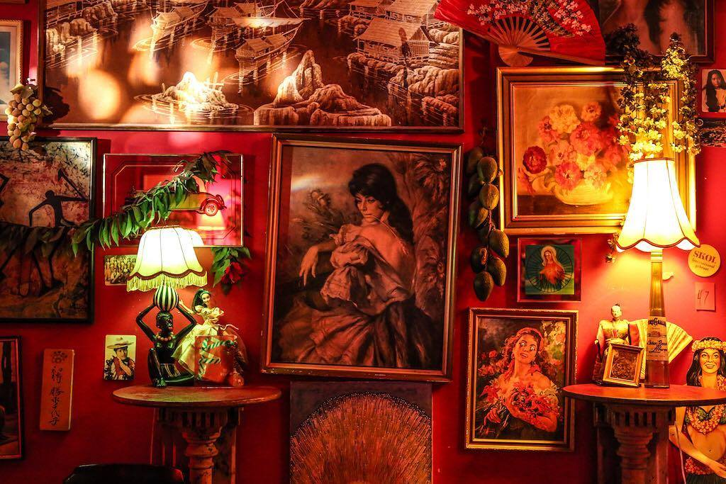 A wall in a dark room with lots of unusual paintings on it and two tables old fashioned lamps