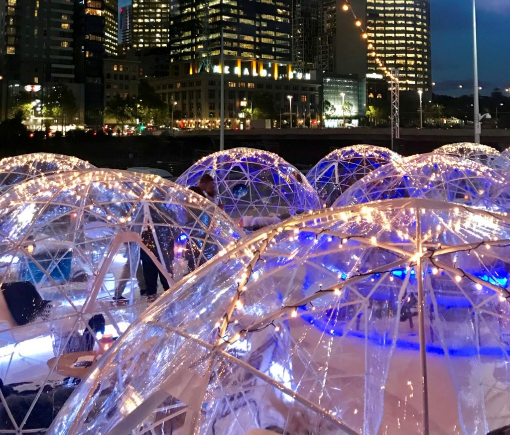 Plastic igloos set up in front of the city skyline at night