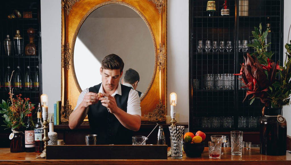 A bartender mixing a drink behind the bar