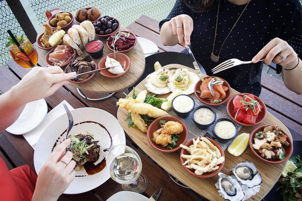 Shot from above of a restaurant table with two people sitting either side. The table is filled with two mezze plates filled with seafood, antipasto, fries, bread and more.