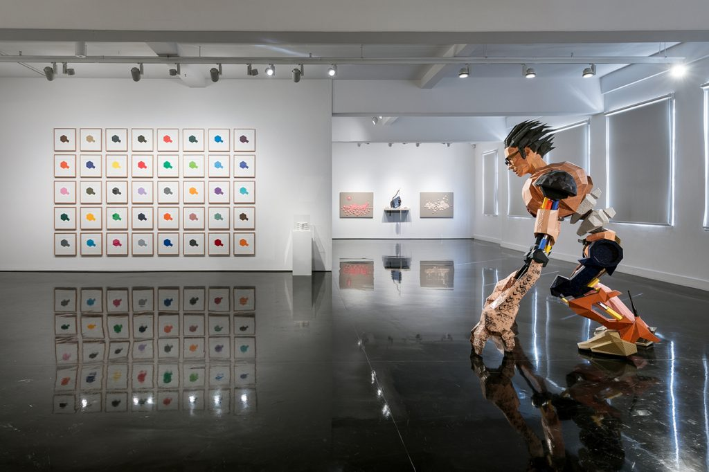 A sculpture of a man and paintings in a modern art gallery space