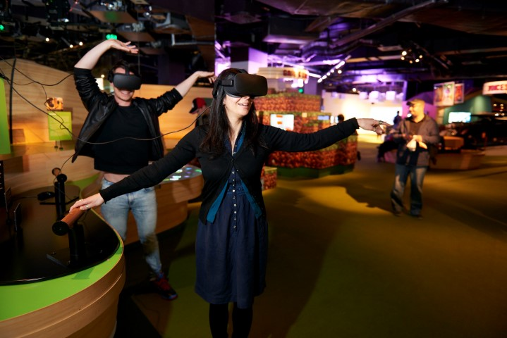 Two people wearing virtual reality goggles in a gallery