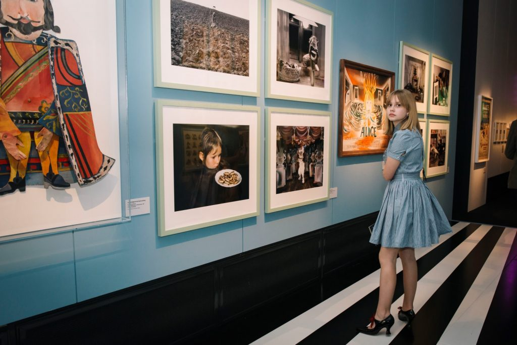 A girl standing in an exhibition looking at pictures