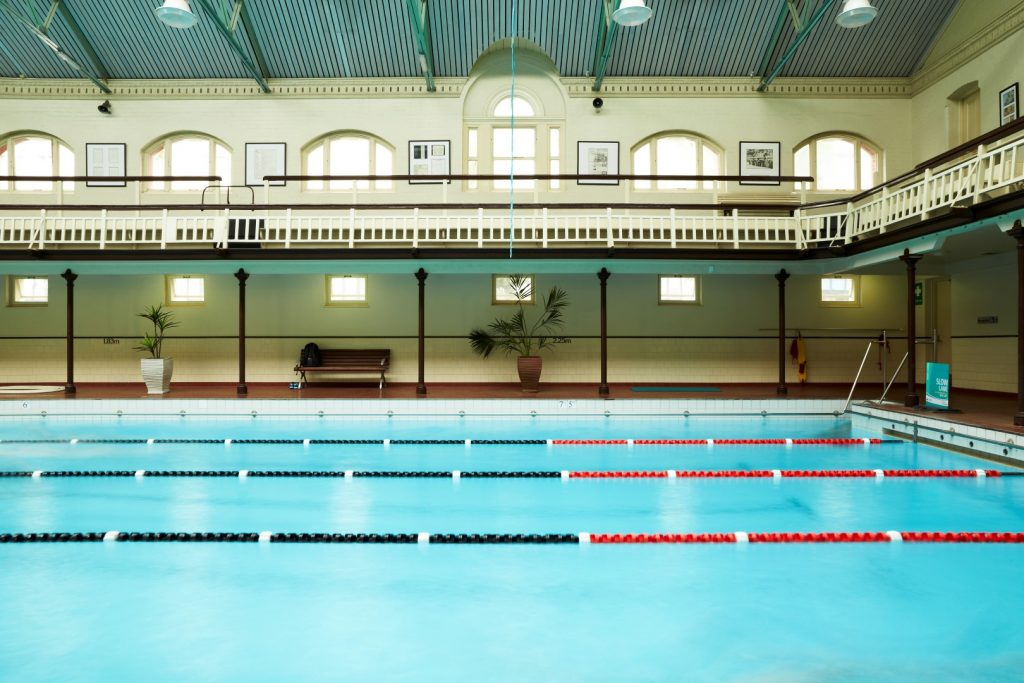 A large blue swimming pool inside an historical building