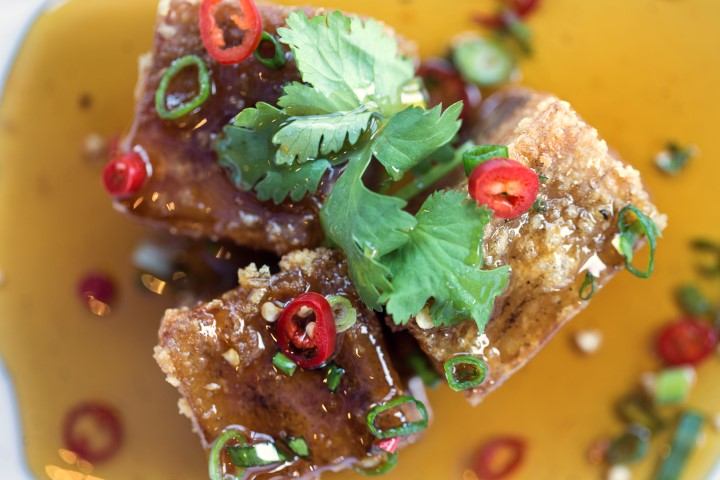Three pieces of pork belly covered with chillis, coriander and chilli sauce