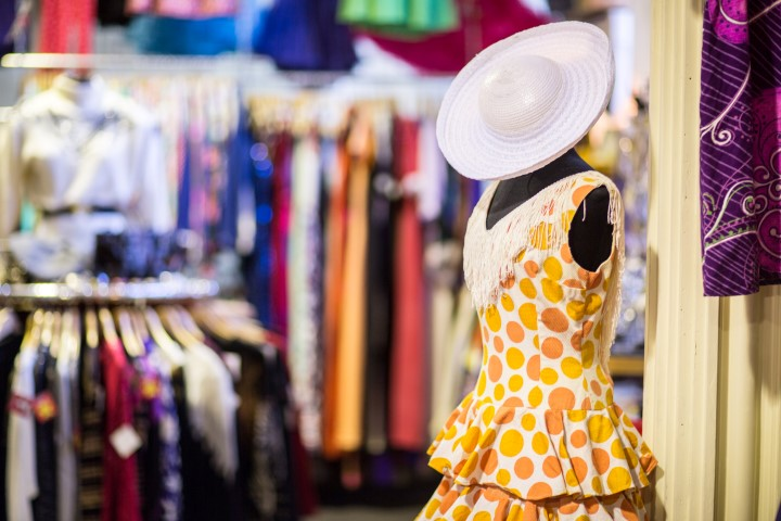 An old fashioned dress and sun hat on a mannequin in a vintage clothing shop