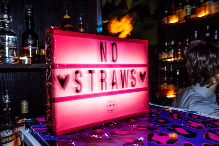 A neon sign in a bar that says no straws