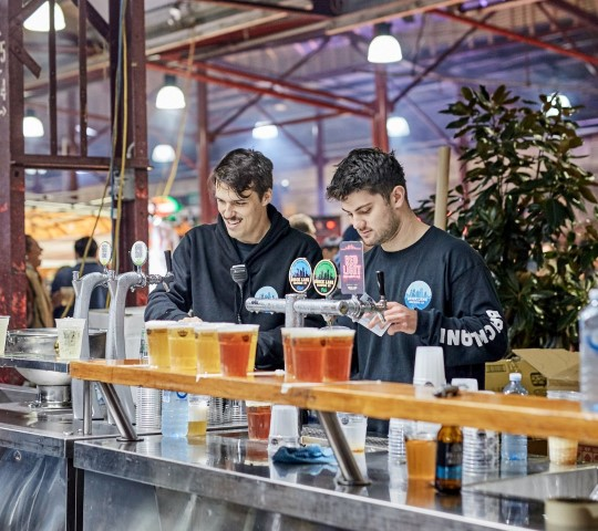 Two men pouring beers at a bar at a market