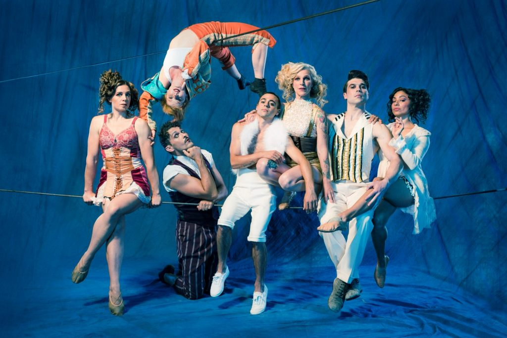 A group of circus performers in various quirky outfits