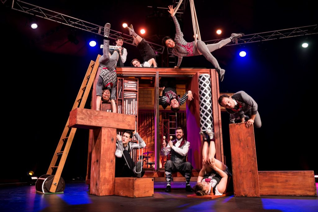 A group of acrobatics performing various tricks on a stage
