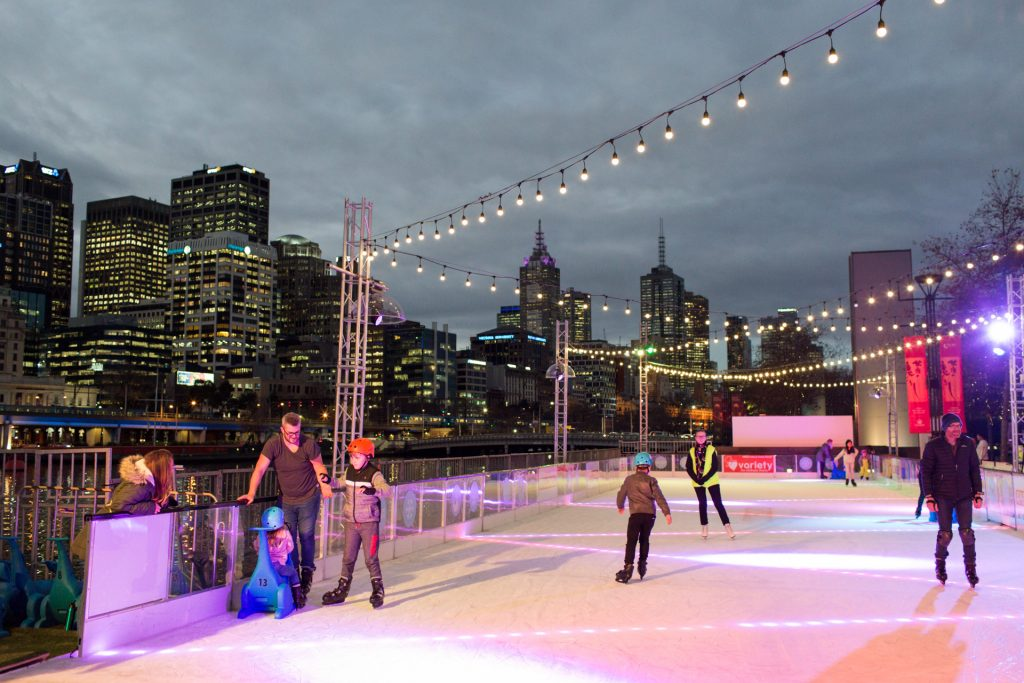 People ice skating on an outdoor ice rink at night with the city skyline in the background