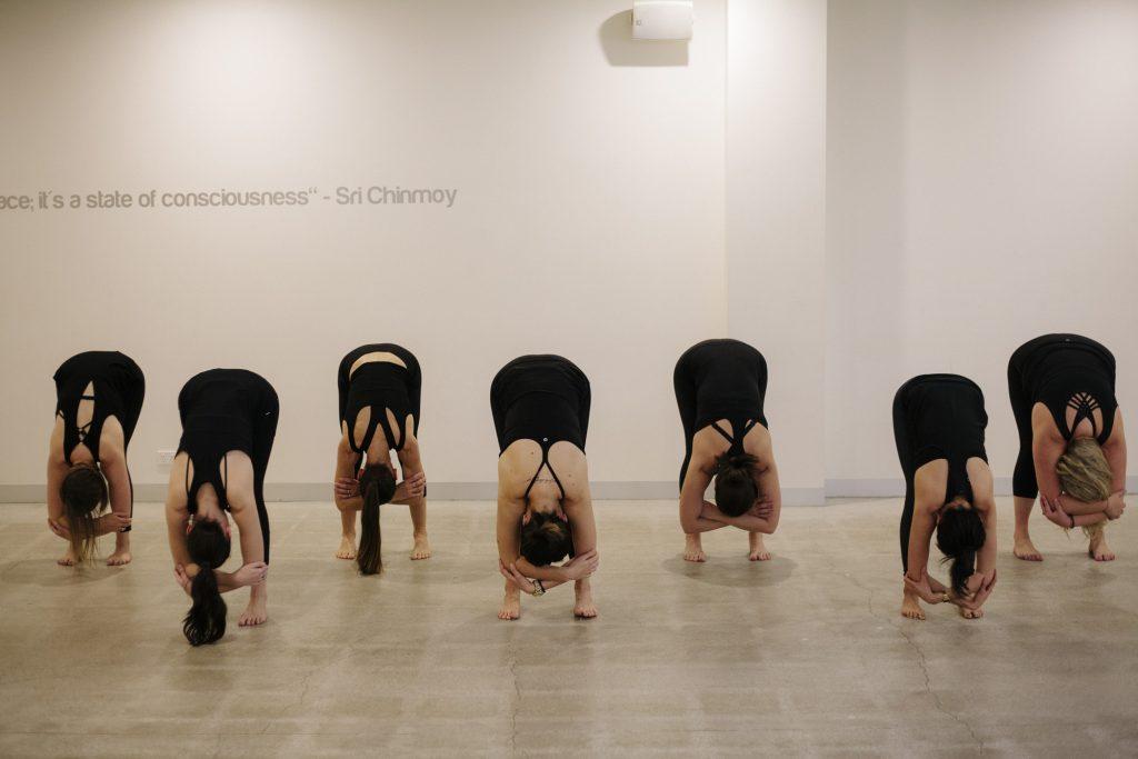 seven women doing yoga in studio