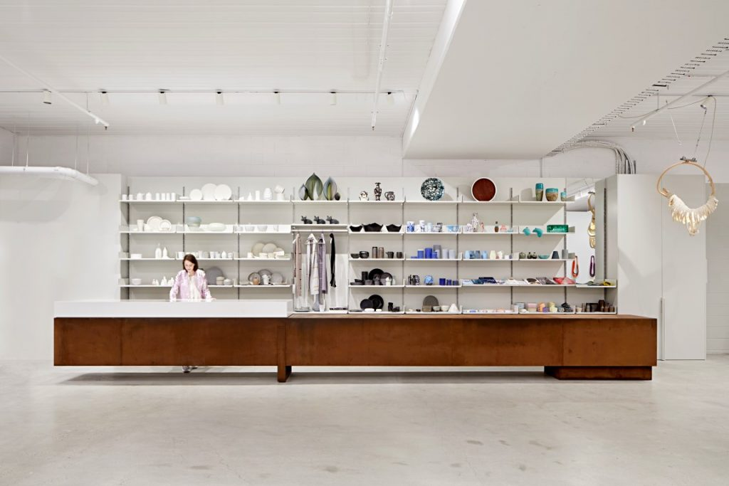 A white room with a long wooden bench in the middle. Shelves behind the bench holding small coloured objects.