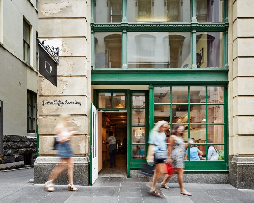 Photo of cafe of Melbourne street with green window frames and three people walking past out the front.