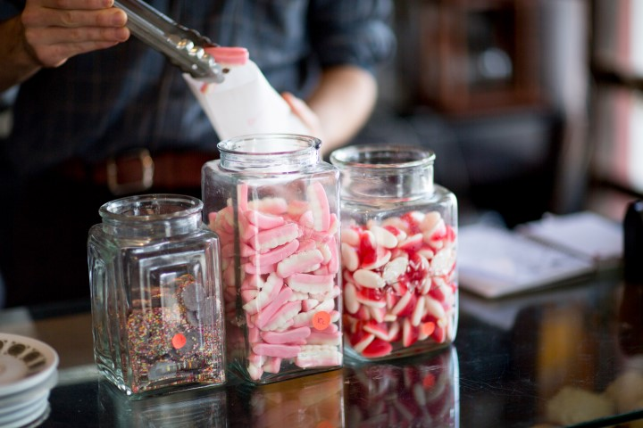 Three glass jars filled with sweets on a shop counter and a hand holding tongs and putting sweets into a paper bag