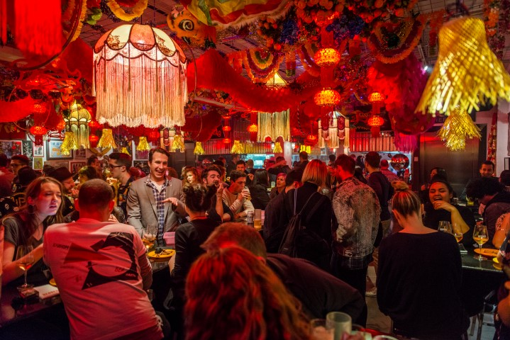 A red and neon lit room crowded with people enjoying food and drink