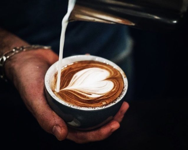 Pouring coffee into a coffee cup held in persons hand, making heart shaped latte art