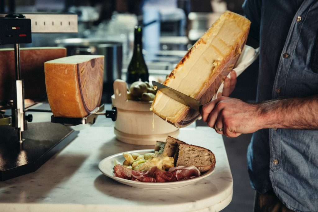 A melting half wheel of cheese being scraped over a plate of meat and vegetables