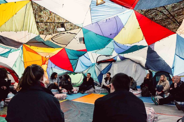 People sitting on the floor inside a multi coloured tent