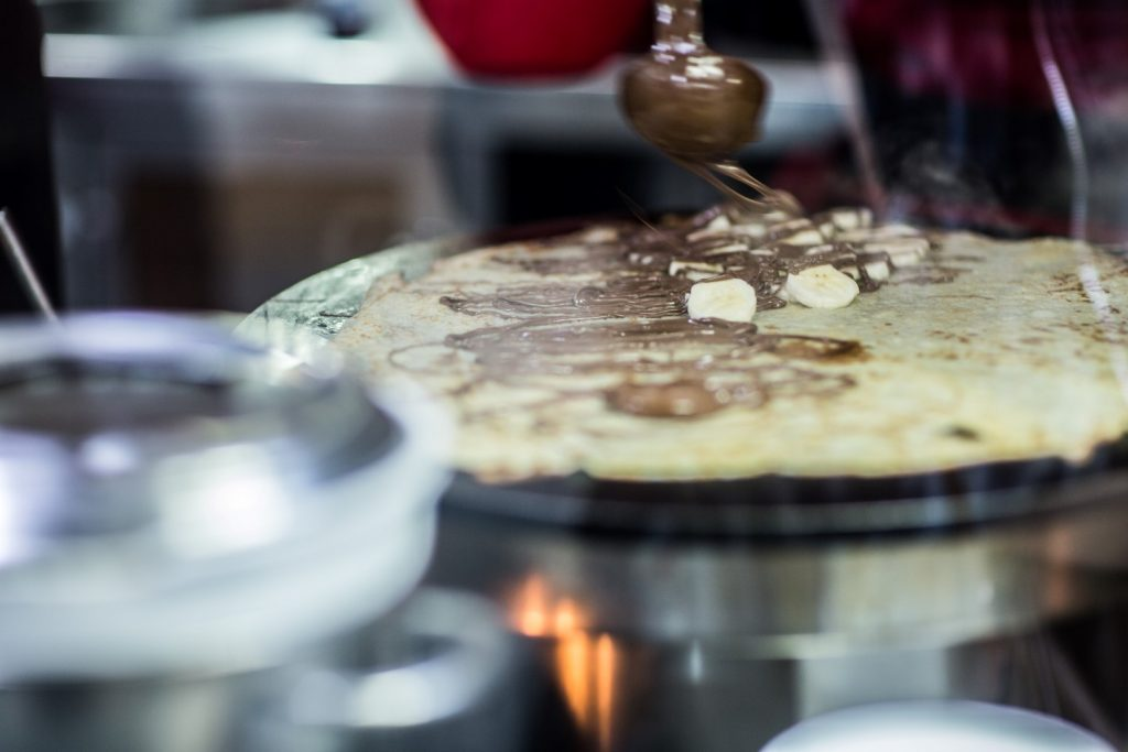 A crepe with bananas on top being cooked on a hot plate with a ladle spooning chocolate sauce onto it