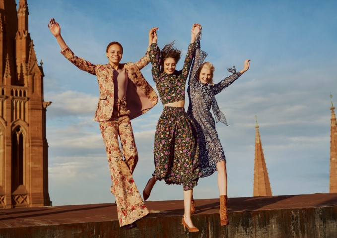 Three women holding hands and jumping in the air