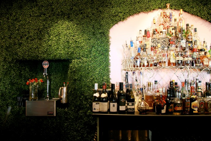 A bar with astr turf on the walls and shelves of drinks
