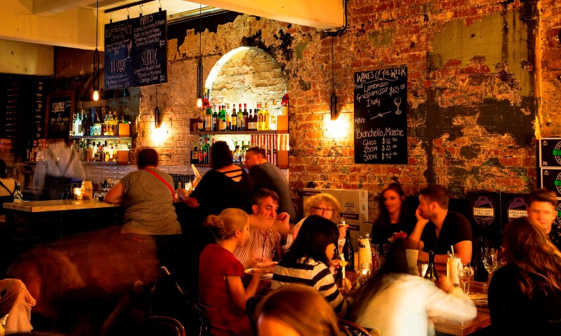 People eating and drinking in a crowded bar