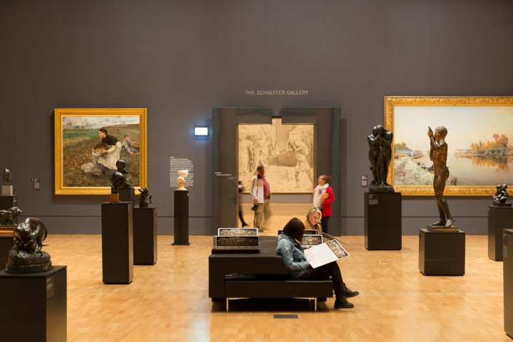 A woman sitting reading in the middle of an art gallery
