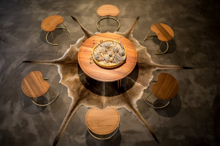 A wooden table sitting on top of an animal skin and surrounded by six stools