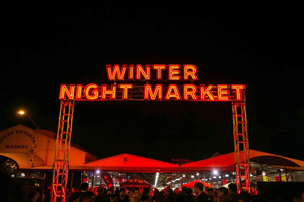 A large red neon sign spelling out 'Winter Night Market' suspended above a crowd of people milling about at a night time market