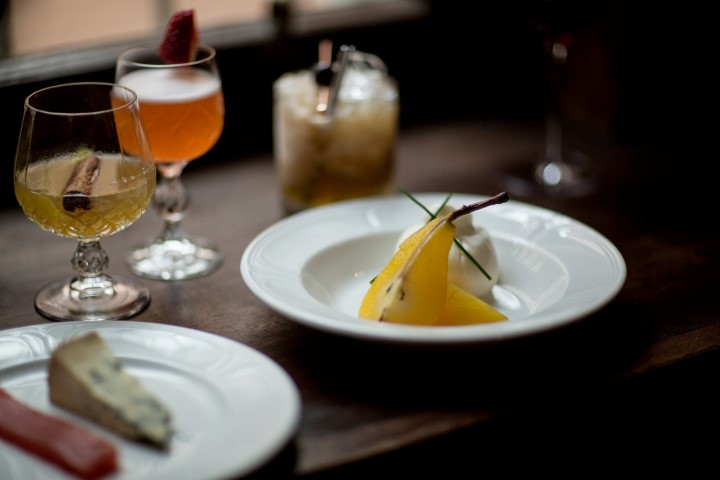A plate of cheese and pears and some cocktails on a table