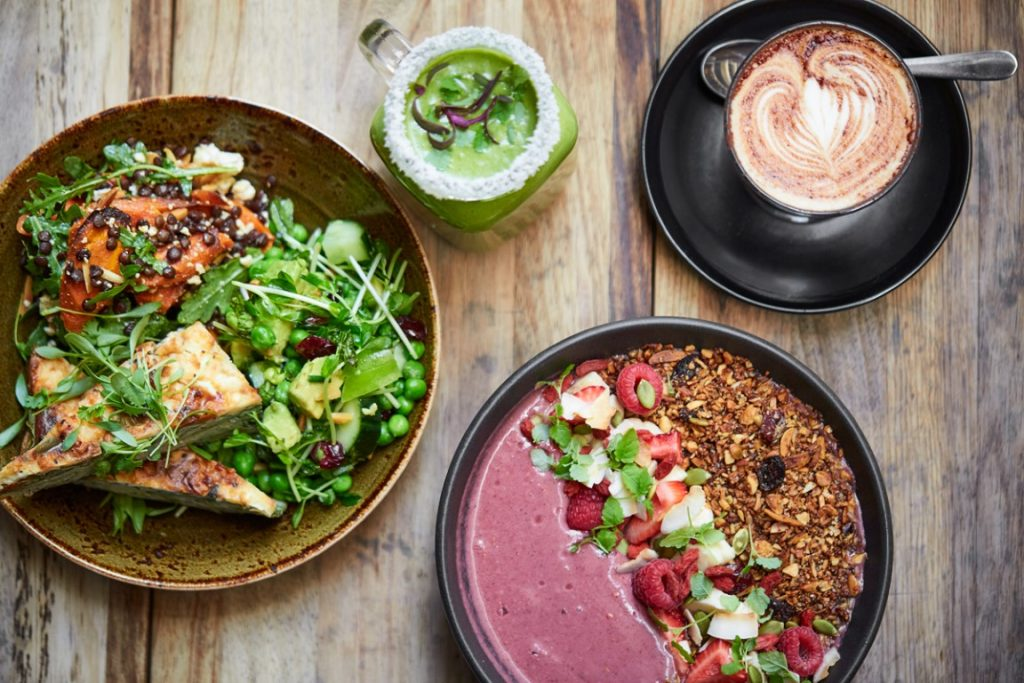 Wooden table with two plates of food, one acai bowl and one with frittata and salad, coffee and green smoothie.