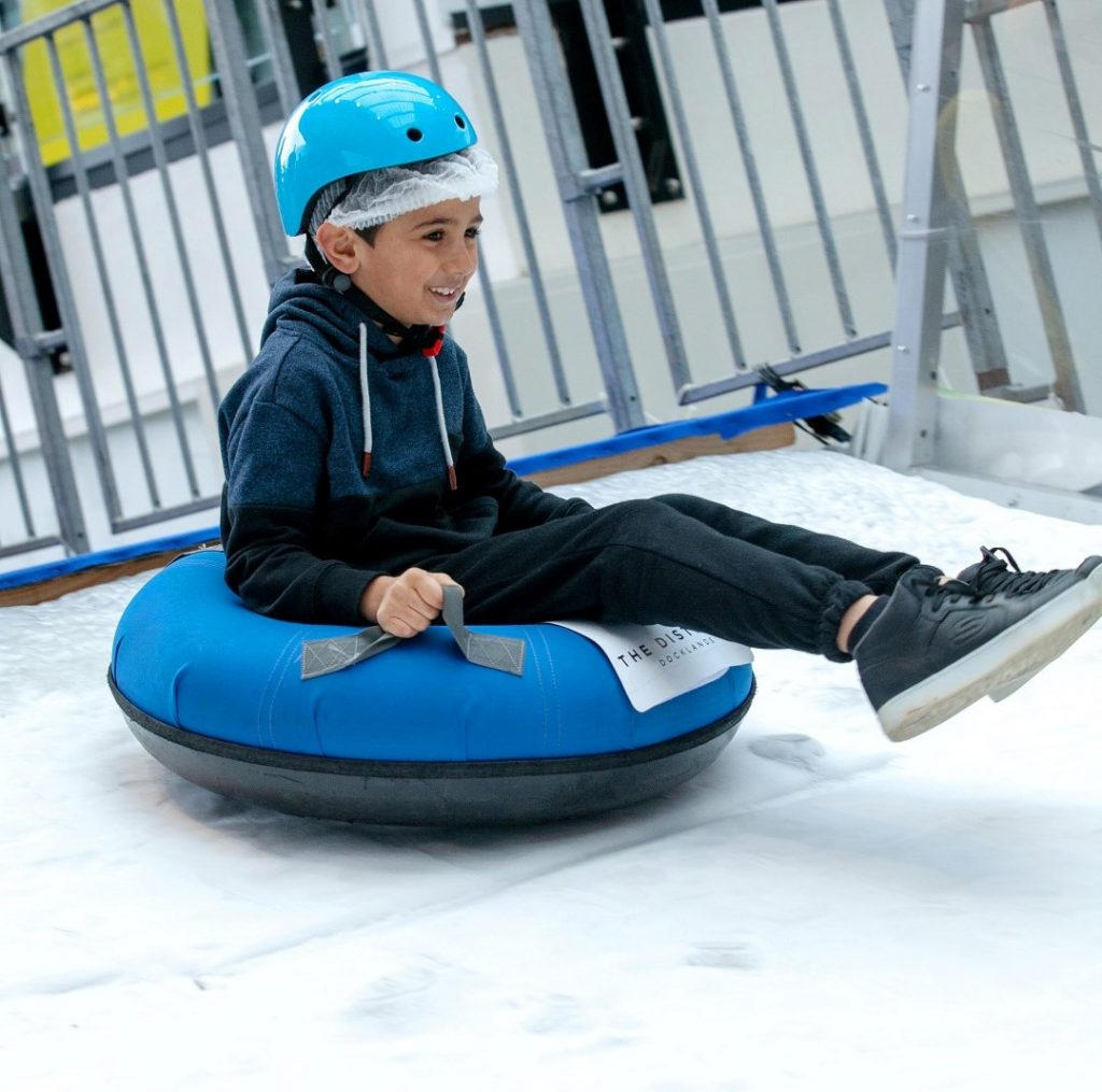 A boy sitting in a inflated tyre sliding down an ice slide