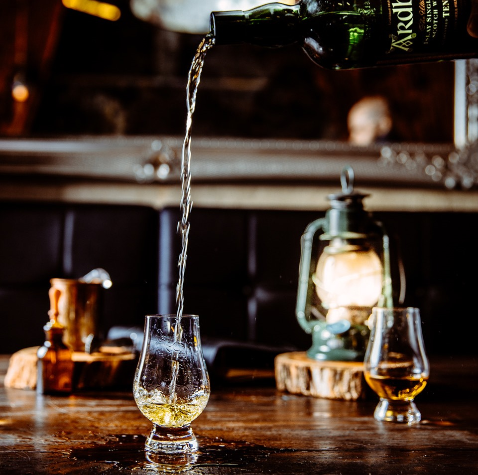 A bottle of whisky pouring into a glass at height on a wooden bench