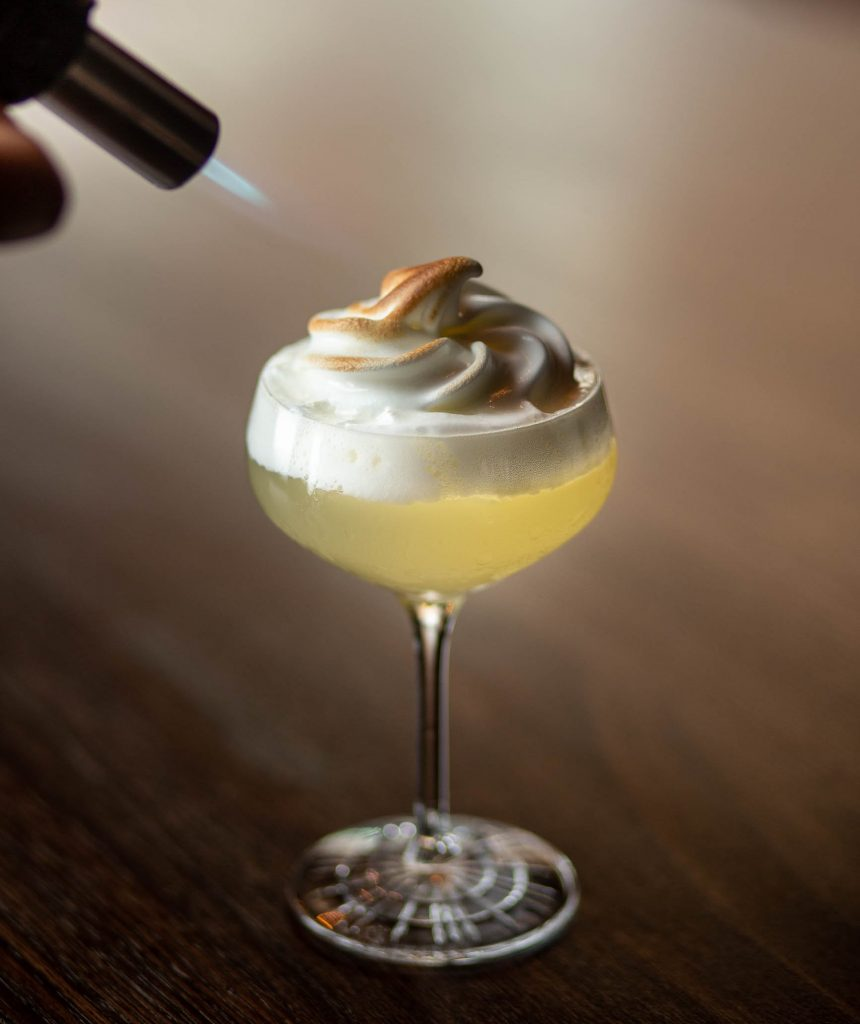 Cocktail in glass with meringue on top being blow torched