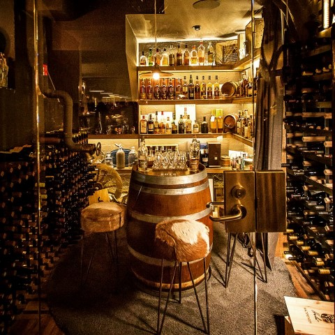 A small sitting area inside a wine cellar. Three stools with cowhide seats around a small barrel, with shelves of whisky bottles behind it.