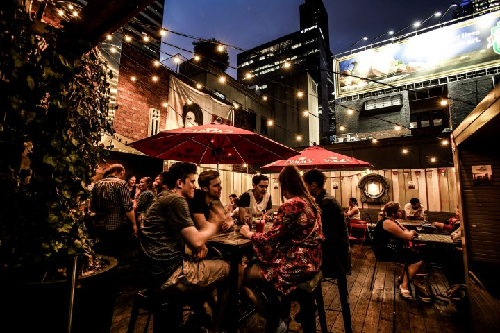 A group of people talking and drinking in a rooftop bar under fairy lights at night