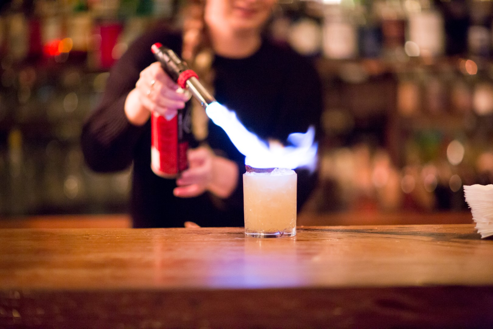 A woman at a bar holding a blowtorch over a cocktail
