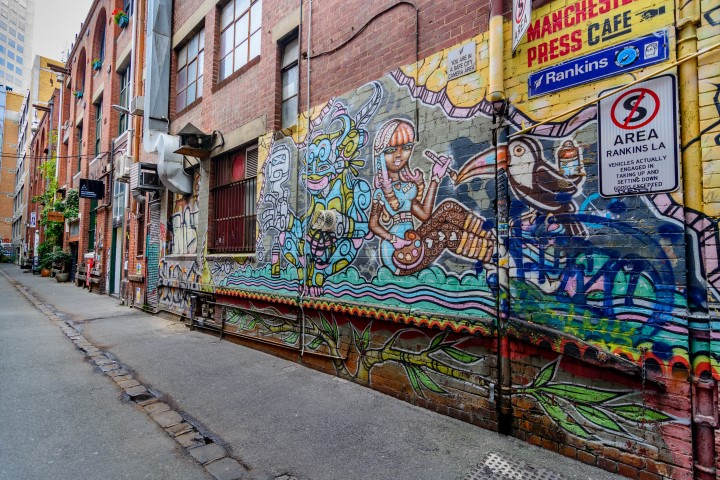 A street art mural on a brick wall in a laneway