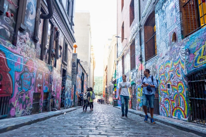A wide laneway with street art on the enclosing walls. Tourists walking down the laneway.