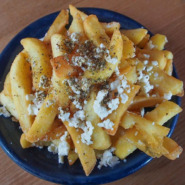A bowl of chips with feta and herbs crumbles over them