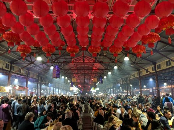 A huge crowd of people eating, talking and walking in a big undercover market Asian lanterns hanging from the ceiling