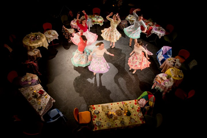 Six women in floral hoop skirts dancing in the middle of a circle of tables.