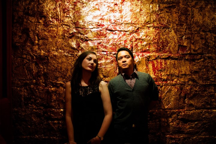 A man and a woman standing in front of a red and gold painted brick wall.