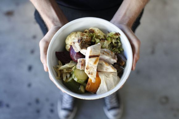 A bowl of food held out by two hands
