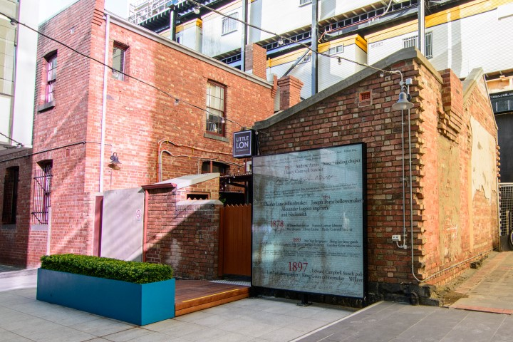 A brick building with a grey roller door at the end of a laneway.